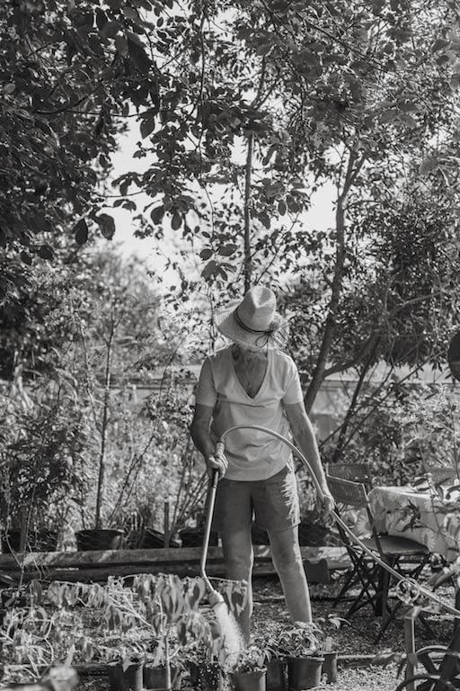 woman watering plants in plant nursery