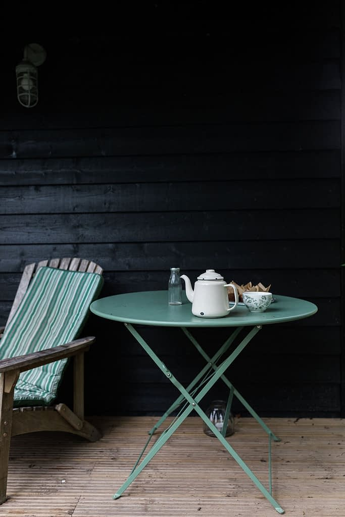Zinc table on terrace with enamel teapot and tea cup