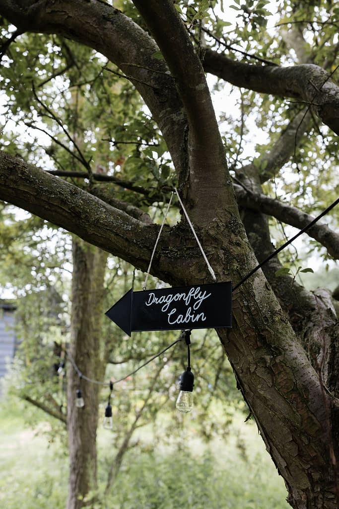 black slate sign hanging off a tree for Dragonfly Cabin