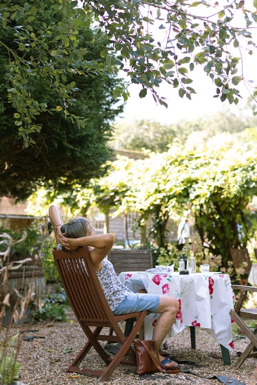 client relaxing a chair outside at the Little Heath Tea room