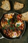 shakshuka tomato based dish in a pan with sourdough bread toasts on the side