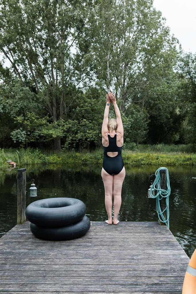 Woman about to dive into natural pool, Cambridgeshire
