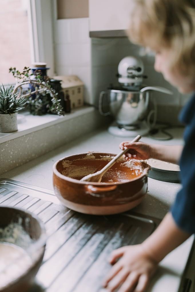 Little girl mixing batter of sweet geranium and blackberries cake