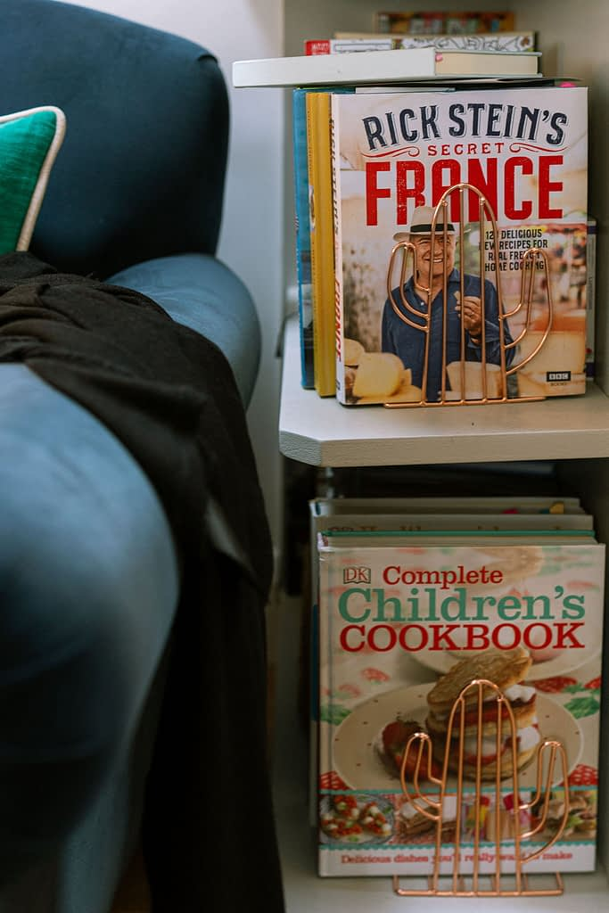two shelves of cookbooks inear armchair