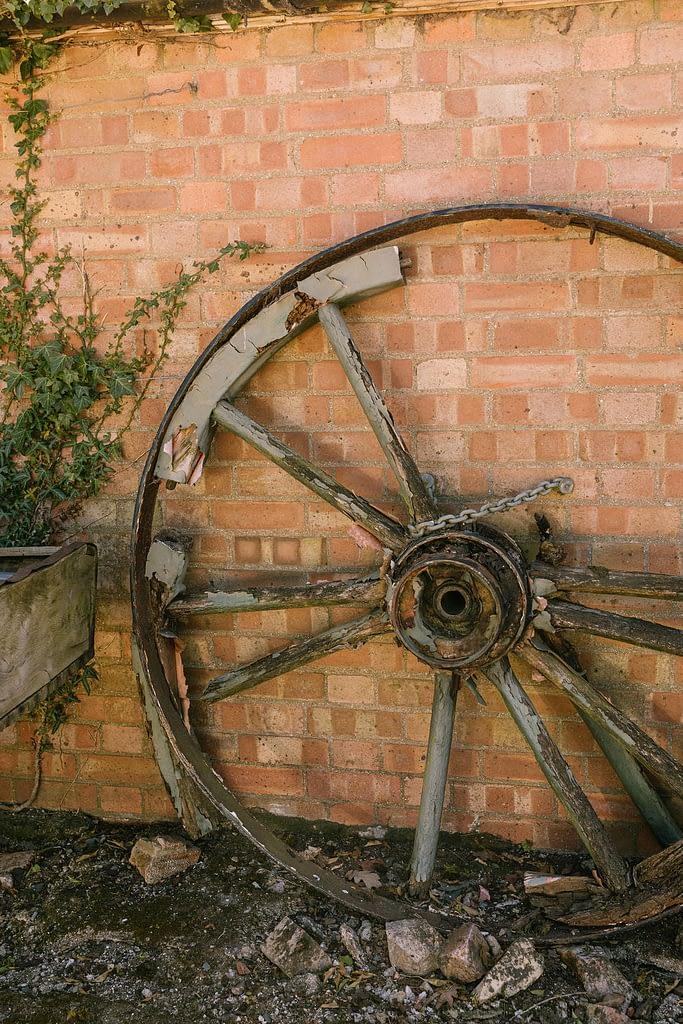 Cart wheel against a brick wall