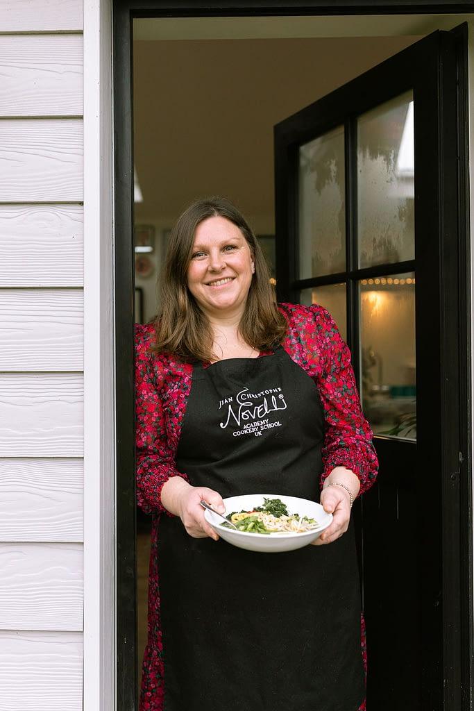 Woman in a doorframe holding a ramen bowl
